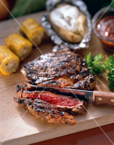 Partially Sliced Rib Eye Steak with a Knife