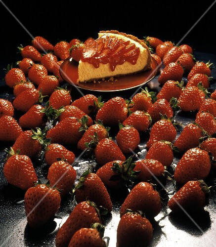 A Slice of Strawberry Cheesecake Surrounded by Strawberries