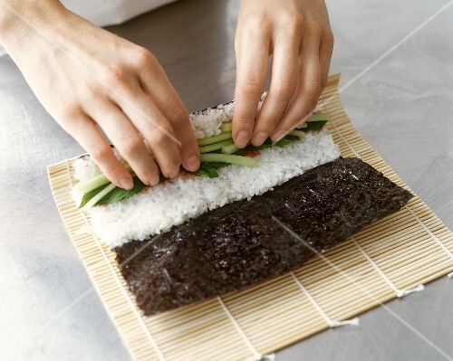 Making Maki Sushi: Hands Rolling Vegetable and Rice Filled Nori