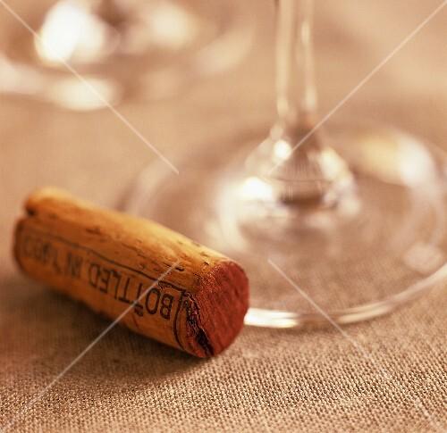 A wine cork beside the stem of a wine glass
