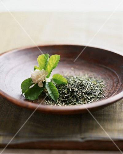 Close Up of a Bowl of Loose Oolong Tea Leaves with Jasmine Flower