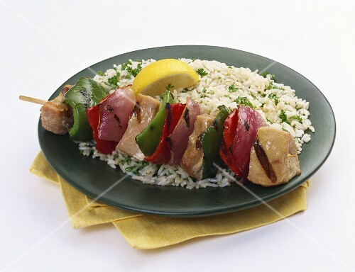 A Chicken Kabob with Bell Pepper and Red Onion Over White Rice