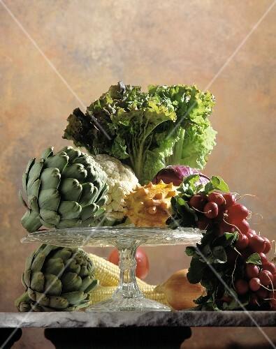 Stillleben mit Gemüse und einer Kiwano auf Kuchenplatte