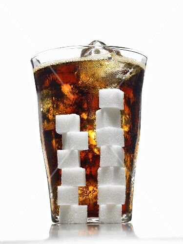 Glass of Cola with Ice; Stacked Sugar Cubes In Front of Glass; White Background