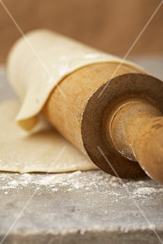 Floured Pie Crust Dough Around a Wooden Rolling Pin; On Stone