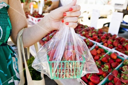 Woman Purchasing Fresh Strawberries at a Farmer's Market; Holding Container of Strawberries in a Plastic Bag