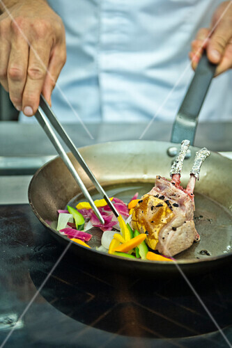 Chef preparing roasted lamb chops and vegetables, Hotel Castagnola, Lugano, Ticino, Switzerland