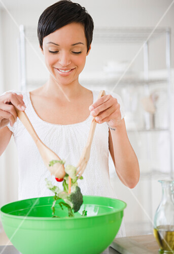Mixed race woman mixing salad in kitchen, Jersey City, New Jersey, USA