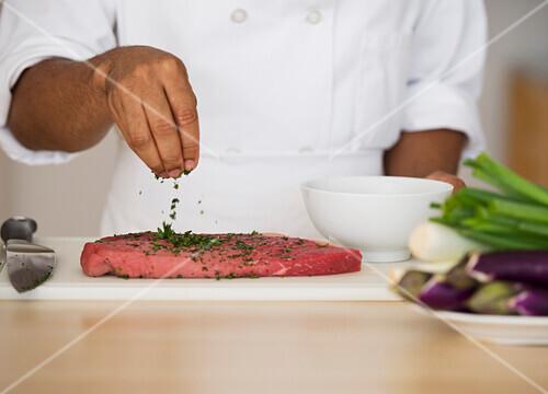 Mixed race chef seasoning steak, Jersey City, New Jersey, USA