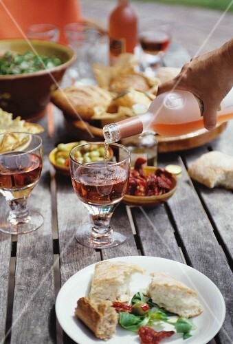 A table laden with antipasti and rosé wine in a garden