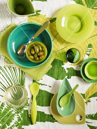 Green plates, glasses and bowls with green olives and a green patterned table cloth