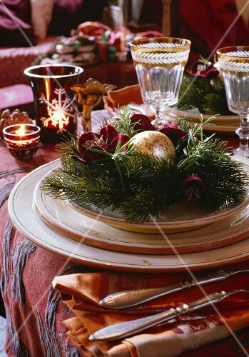 Christmas decorations on a place setting with wine glasses