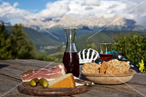 South Tyrolean snack with cheese, bacon, Schuettelbrot and red wine, Trentino, Italy