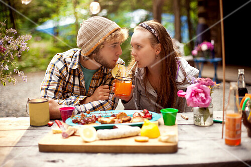 Couple sharing soda at picnic table in forest