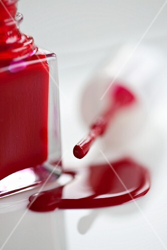 Red nail varnish, an open bottle and a brush