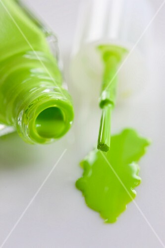 Green nail varnish, an open bottle and a brush