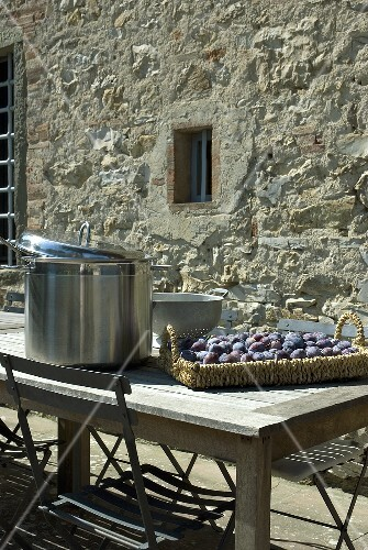A wicker tray of damsons on a wooden table on a terrace